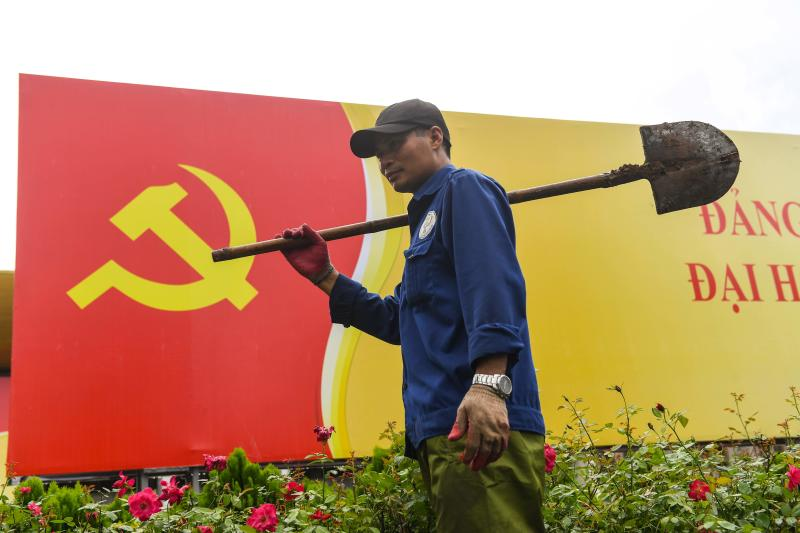 A worker walks past a signboard with the Communist Party flag in Hanoi on Monday, as the city prepares for the upcoming party congress. (AFP photo)