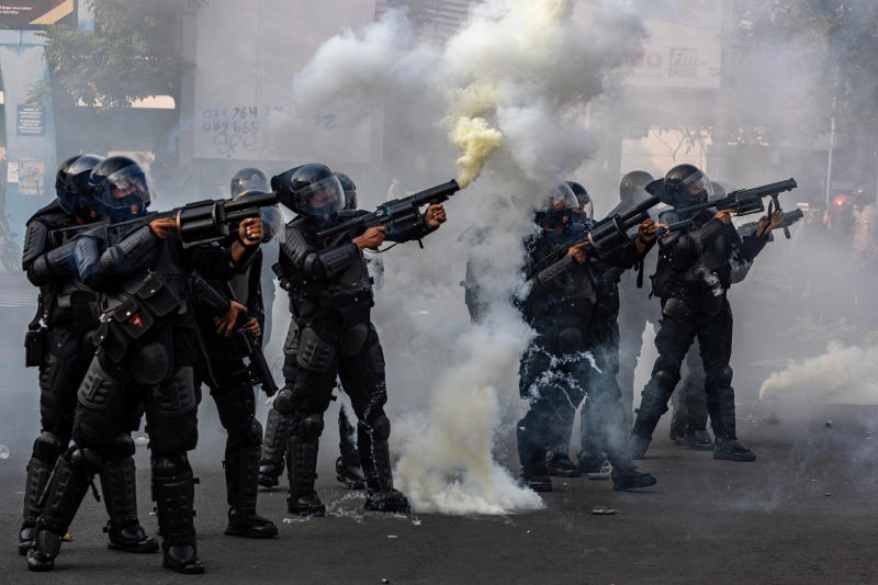 A riot police officer fires tear gas following a protest against the government's labour reforms in a