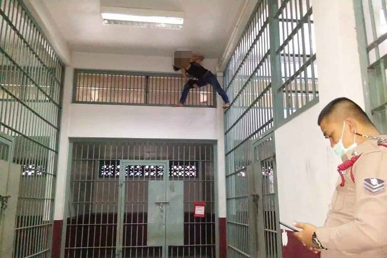 Ploypatcha Sukpansila, 37, climbs to the ceiling of her cell and stays there for 30 minutes at the Sutthisan police station in Din Daeng district, Bangkok, on Thursday morning after being arrested with a gun and bullets. (Police TV photo)