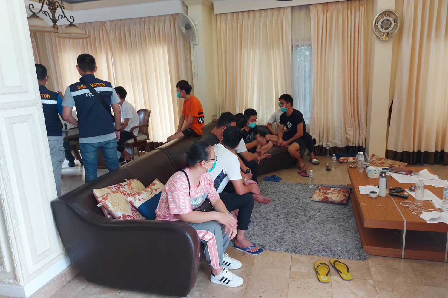 Nineteen Chinese nationals, both men and women, are arrested for illegal entry during a police raid on two houses in Chiang Mai on Thursday. (Photo: Panumet Tanraksa)
