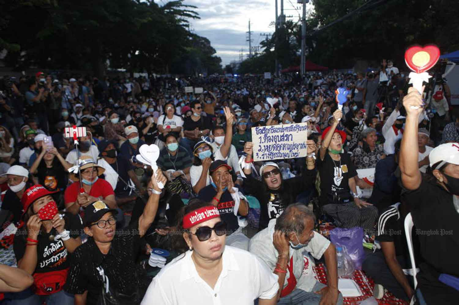 Anti-government protesters sit on the ground outside parliament. They held the rally to monitor parliament's deliberation of charter amendment motions on Sept 24. (Photo: Nutthawat Wicheanbut)