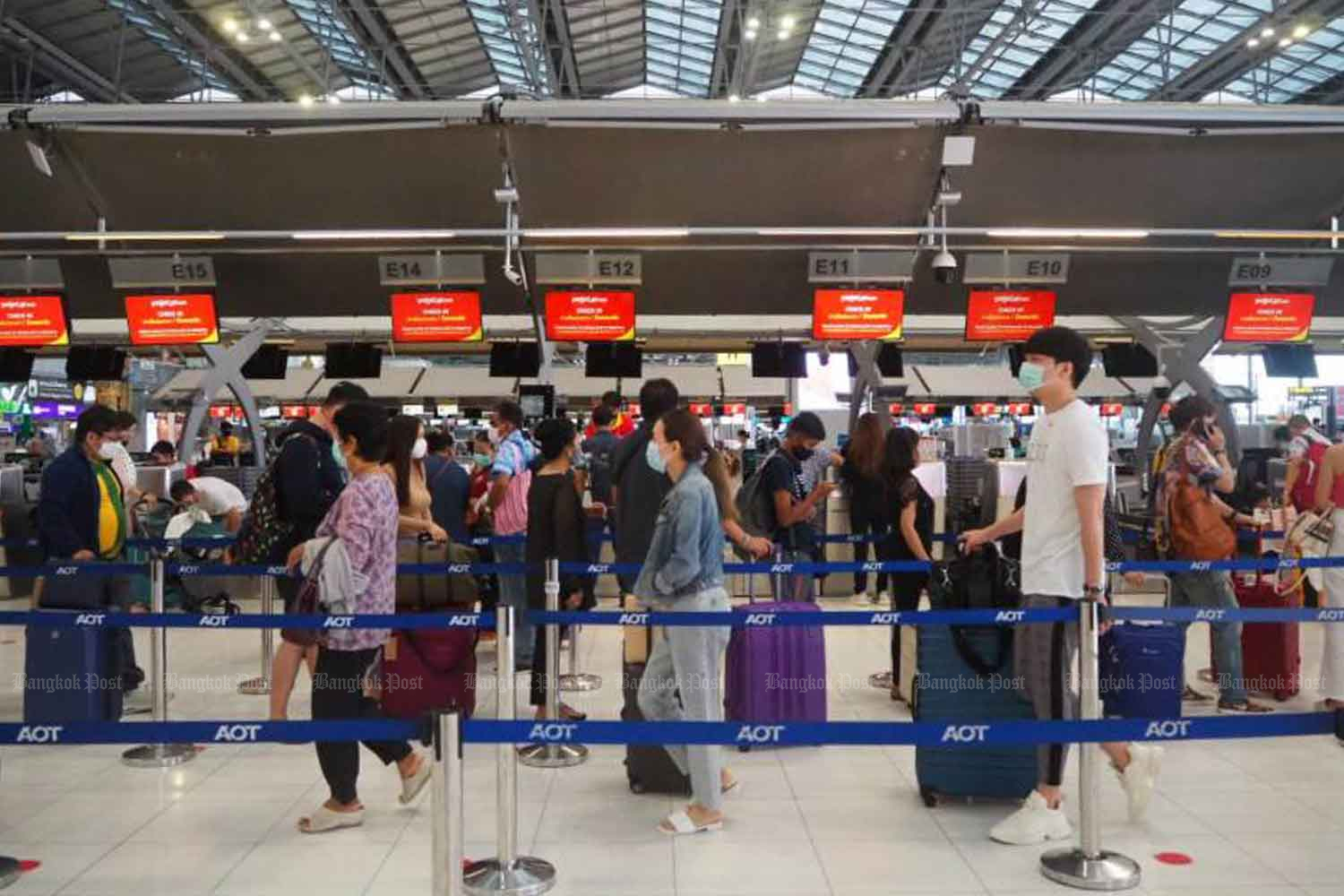 Local travellers queue, with careful spacing, to check-in for domestic flights at Suvarnabhumi airport last month. (Photo: Dusida Worrachaddejchai)