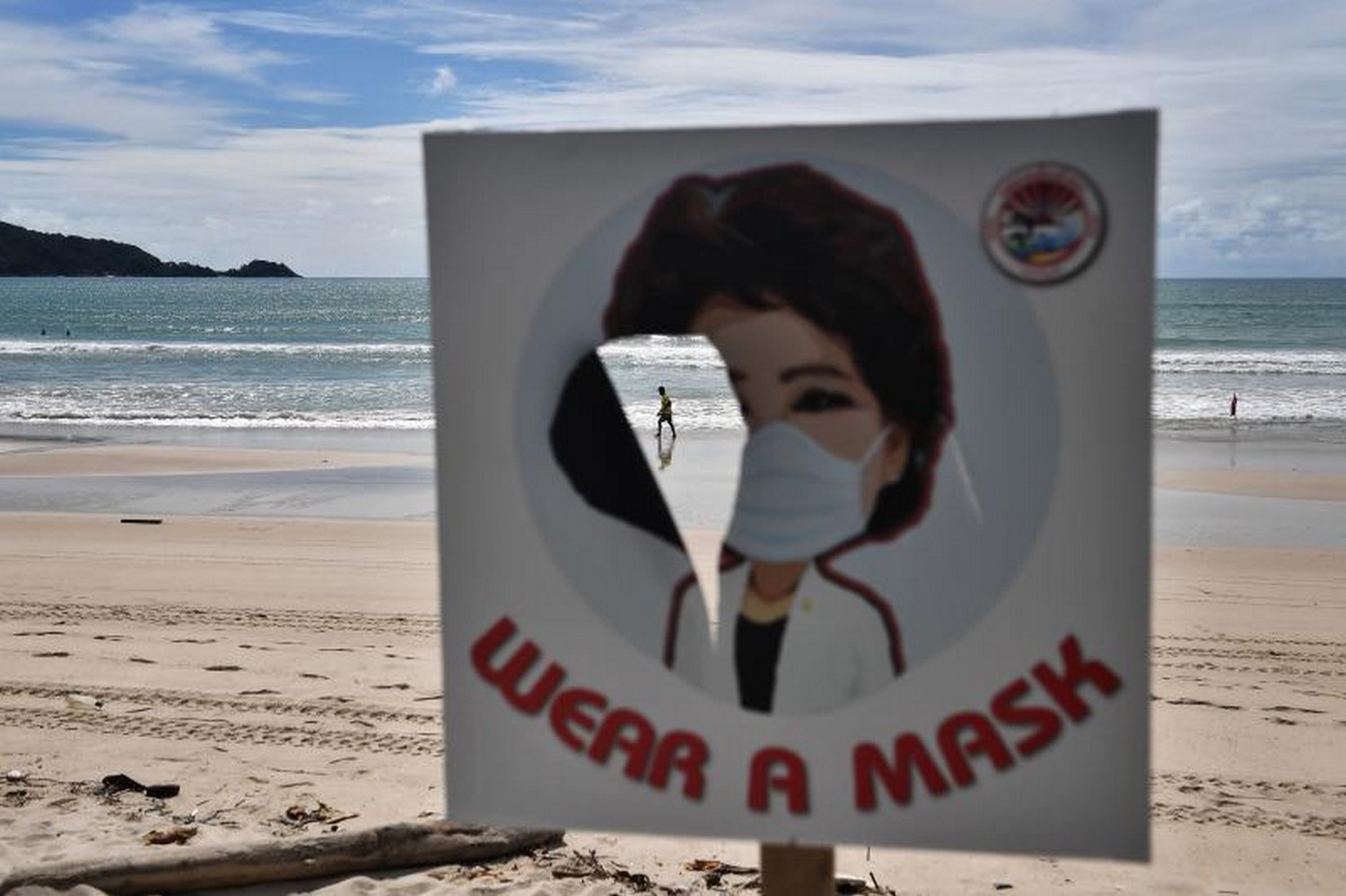 A man walks along the empty beach at Patong, Phuket, seen through a torn sign telling people to wear a mask, on Oct 1. (Photo: Lillian Suwanrumpha/AFP)