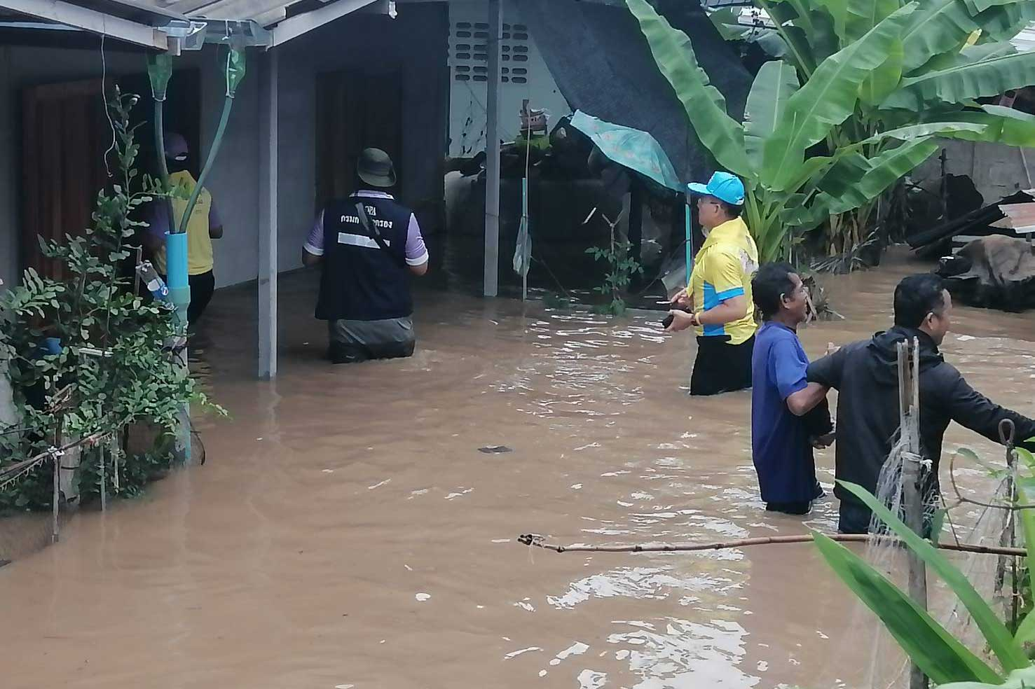 Nakhon Ratchasima governor Wichian Chantaranotha (yellow shirt, centre) wades in water up to his thighs as he leads officials to inspect flooded-houses in tambon Khanong Phra of Pak Chong district on Friday morning. (Photo: Prasit Tangprasert)