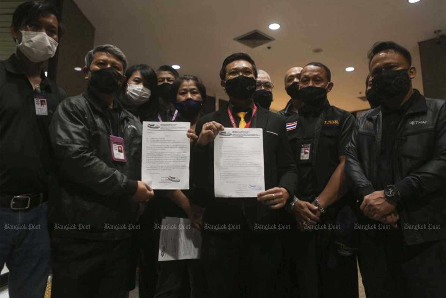 Representatives of the Thai Airways International workers' union and THAI employees show off a letter asking the airline to reconsider the promotions of executives. (Photo: Pattarapong Chatpattarasill)