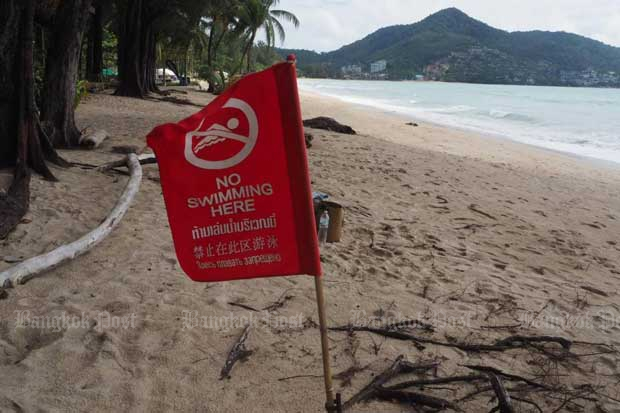 A flag with a 'No Swimming Here' sign has been placed at Phuket's Kamala beach, which is empty of tourists. (Photo by Dusida Worrachaddejchai)