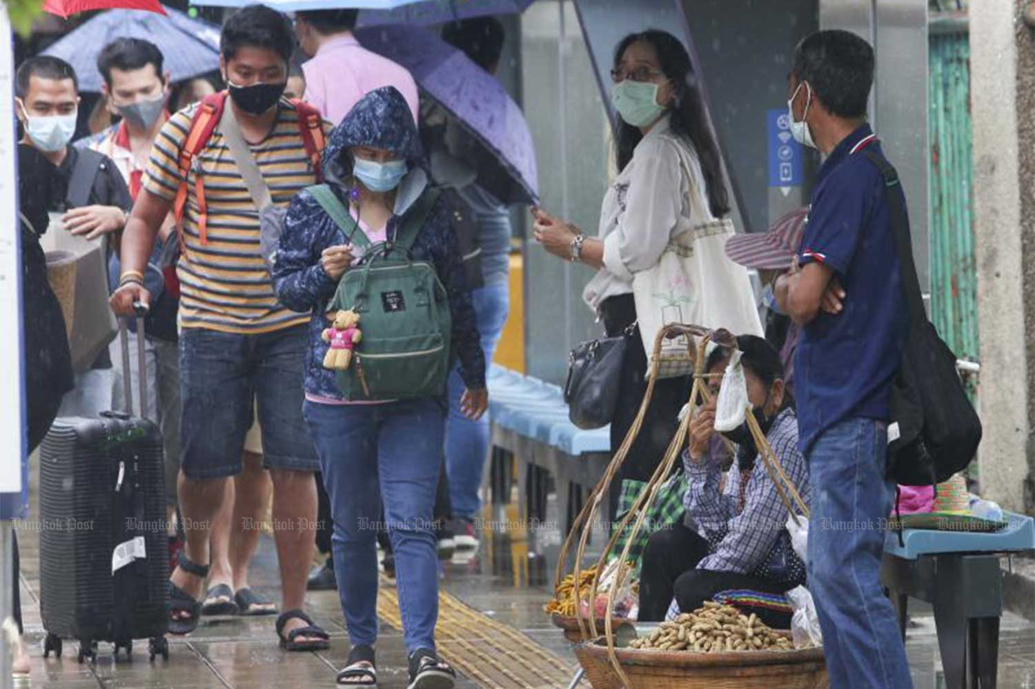 People wearing face masks walk near a bus stop and the Mor Chit BTS Skytrain station in Chatuchak district, Bangkok, as heavy rain pounds the capital on Friday. (Photo: Pattarapong Chatpattarasill)