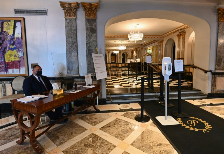 A security officer sits in the lobby of The Pierre hotel, a shadow of its former self amid the coronavirus pandemic