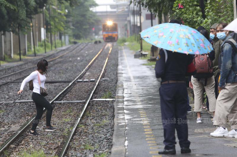 A woman crosses the track at Bang Khen station during the light rain in Bang Khen district on Friday morning. (Photo by Pattarapong Chatpattarasill)