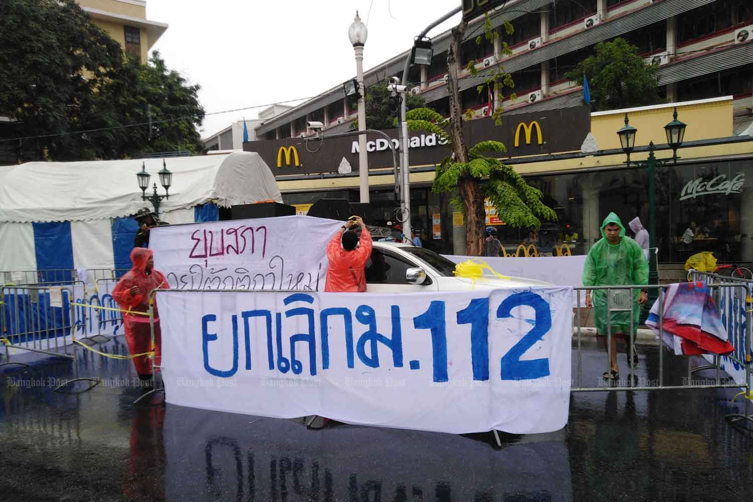 Some demonstrators set up tents occupying one side of Ratchadamnoen Avenue in Bangkok on Tuesday, spreading a banner calling for the repeal of Section 112 of the Criminal Code that protects the royal institution. (Photo by Pornprom Satrabhaya)