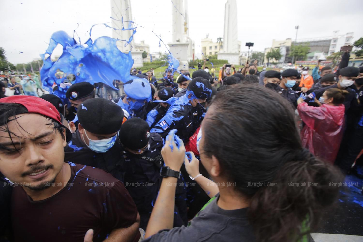 Anti-government protesters splash blue paint on security officers during a scuffle near Democracy Monument on Ratchadamnoen Avenue. Police ordered the protesters to leave as the road was being prepared for Tuesday's royal motorcade. (Photo by Pornprom Satrabhaya)