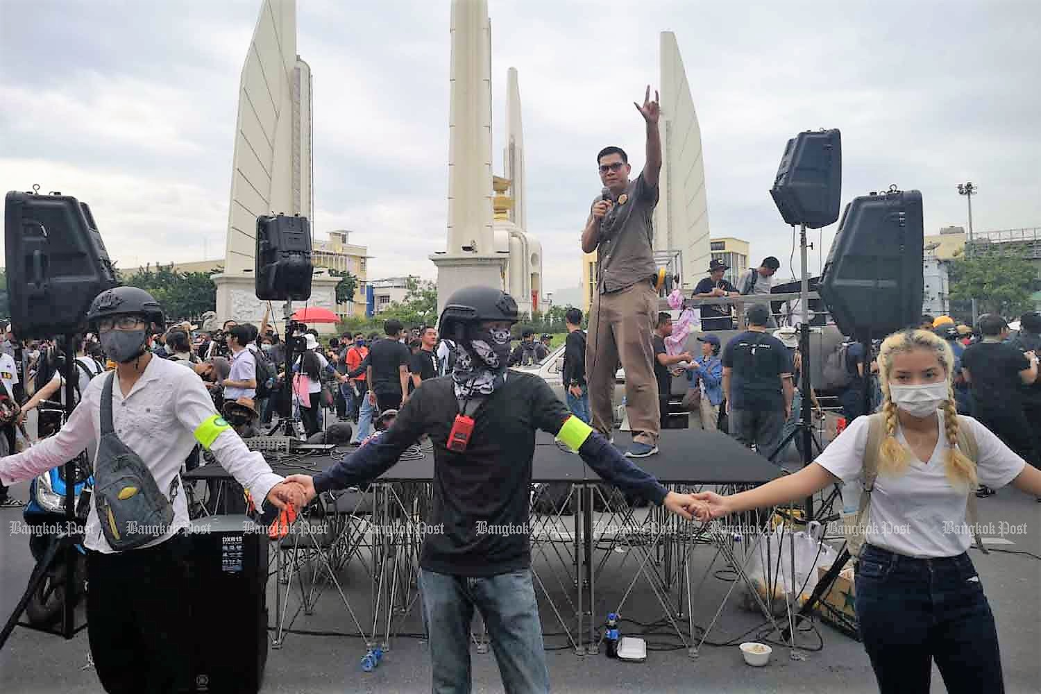 A protest leader goes up a stage at a corner of the Democracy Monument on   Ratchadamnoen Avenue on Wednesday morning, as demonstators form a cordon around the platform. (Photo: Jetjaras Na Ranong)