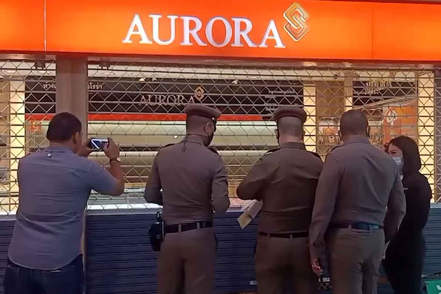 Police at the Aurora gold shop in Big C superstore mall, Rattanathibet, in Nonthaburi, after the holdup on Wednesday morning. The robber stole 11 gold rings. (Screenshot from Channel 8)