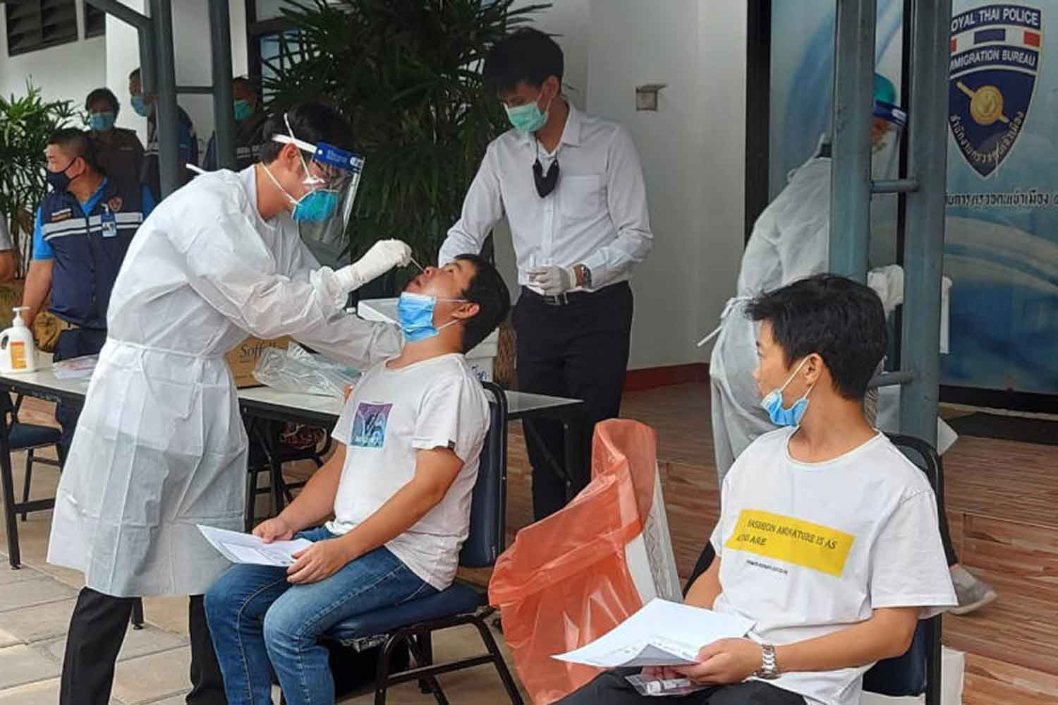 Disease control officials take swabs from migrants in Chiang Mai province last Friday. (Photo: Panumet Tanraksa)