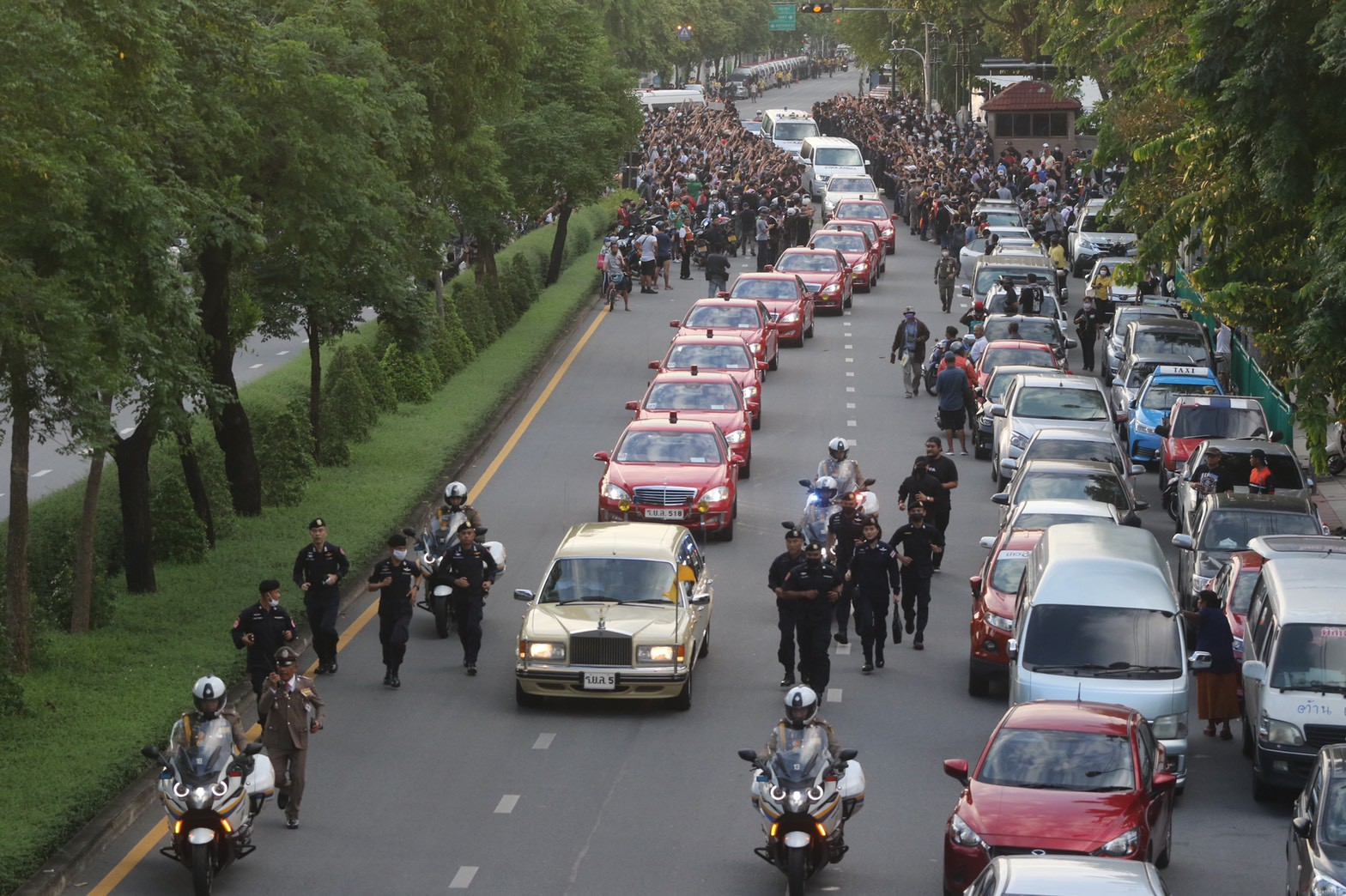 The motorcade carrying Her Majesty the Queen and His Royal Highness Prince Dipangkorn Rasmijoti passes through demonstrators near Government House on Wednesday evening. (Photo supplied)