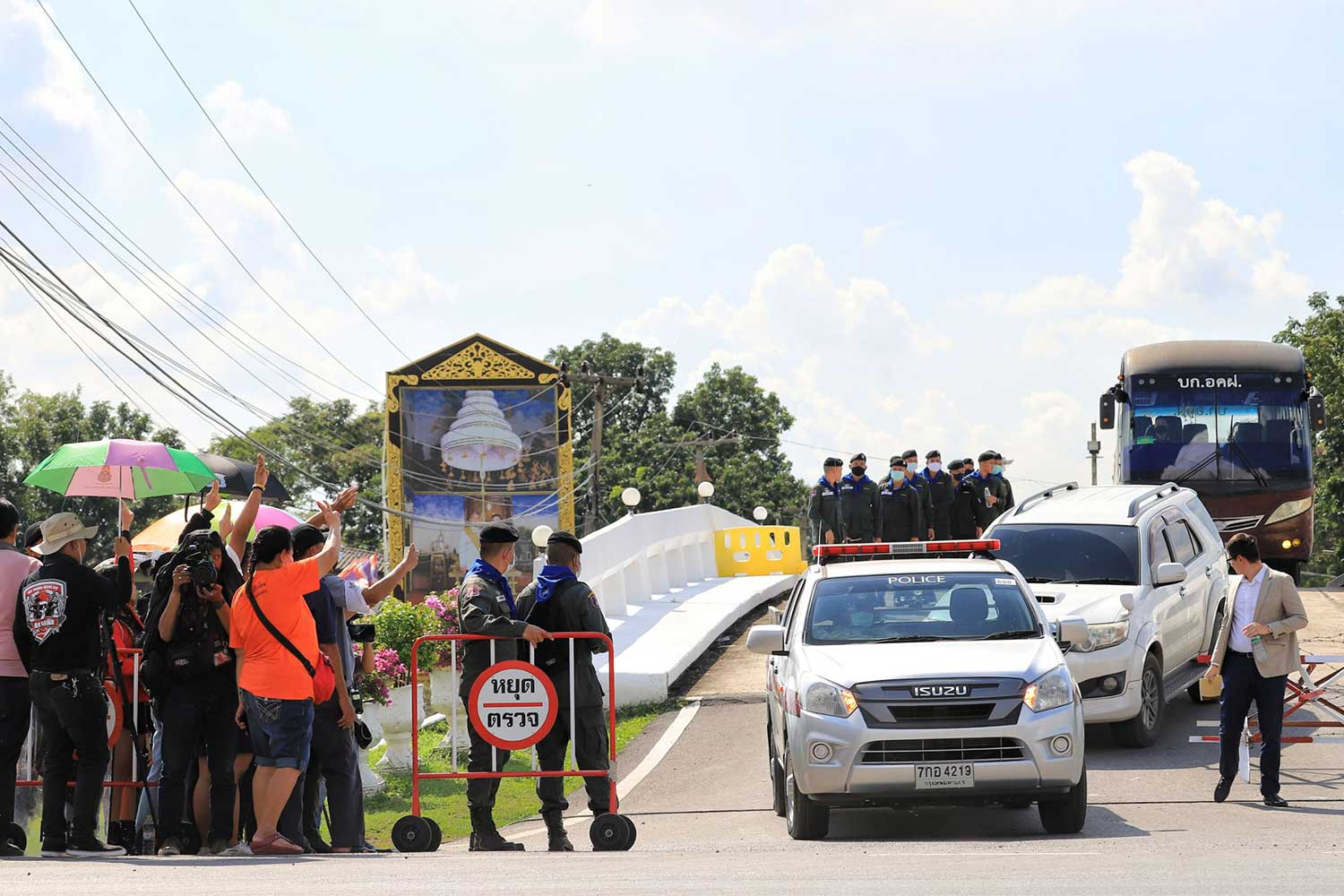 Supporters of the pro-democracy movement raise a three-fingered salute as police vehicles transport three rally leaders to the Thanyaburi Court in Pathum Thani on Thursday afternoon. (Photo: Pongpat Wongyala)