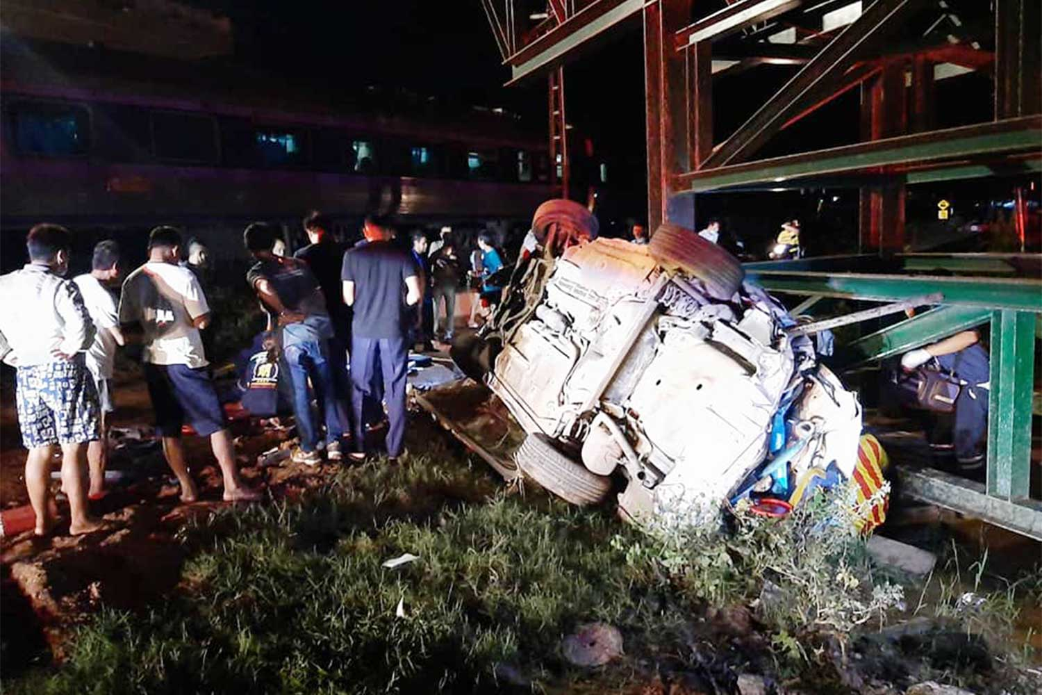 The crumpled Toyota Vios after it was hit by a train at an unguarded crossing in Khao Yoi district, southern Phetchaburi province, on Thursday night. A woman passenger as killed and two men injured. (Photo: Sawang Sanphet rescue foundation Facebook page)