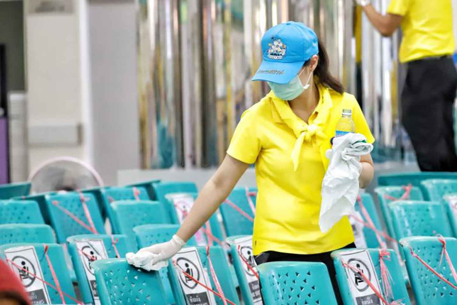 Volunteers disinfect chairs at Pathum Thani Hospital in Pathum Thani province, to help control Covid-19. (Photo: Pongpat Wongyala)