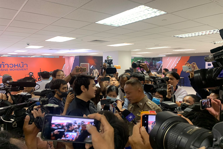 Progressive Movement co-founder Piyabutr Saengkanokkul talks to a police officer from Makkasan station during the search at the Progressive Movement office in the Thai Summit building on Friday. (Photo: @ProgressiveThai Twitter account)