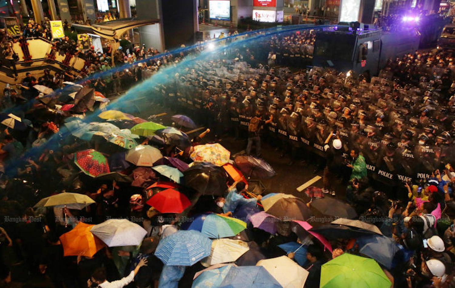Jets of dyed water are sprayed from a water cannon over the heads of riot police officers trying to break up an anti-government rally at the Pathumwan intersection as demonstrators push back on Friday evening. (Photo by Apichit Jinakul)