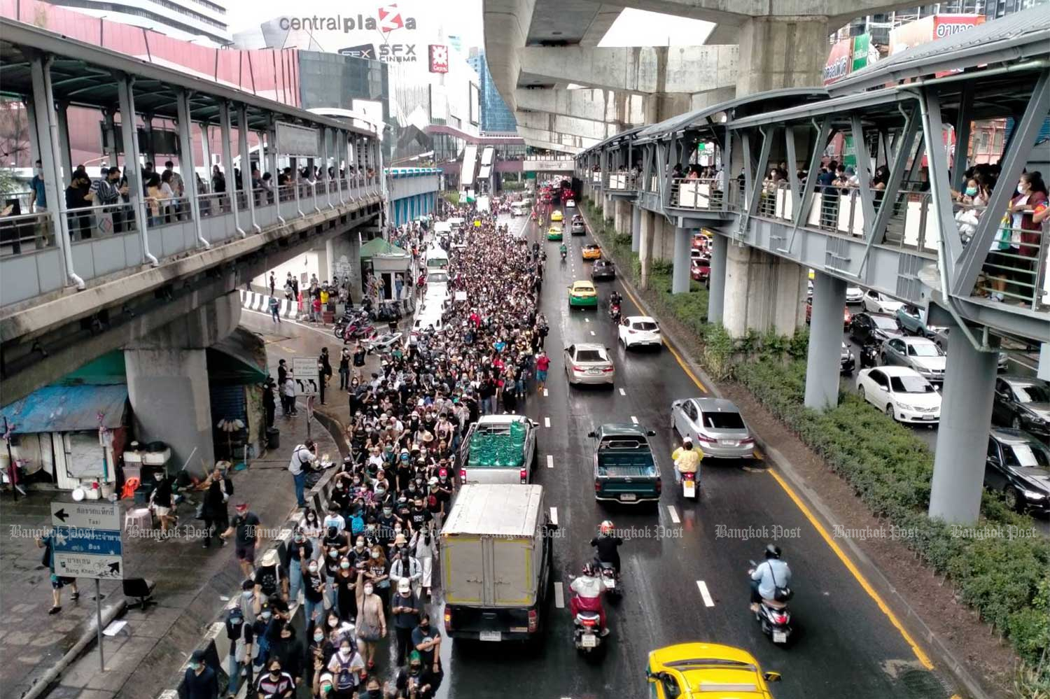Demonstrators begin gathering on Phahon Yothin Road in front of the skywalk at the closed Lat Phrao station on Saturday afternoon. It is one of three sites chosen by protest organisers. (Photo Wichan Charoenkiatpakul)