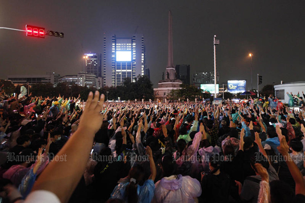 Thousands of students flash the three-finger salute at Victory Monument before the rally ends on Sunday. (Photo by Wichan Charoenkiatpakul)