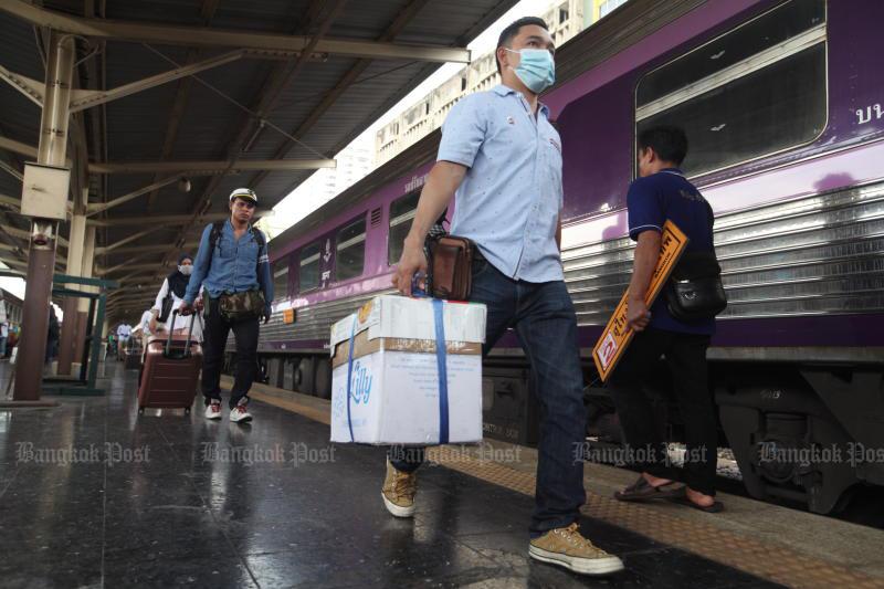 A passenger wearing a face mask disembarks from a train at Hua Lamphong station. (Bangkok Post file photo)