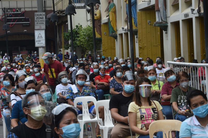 Catholic faithful sit outside the Quiapo church in Manila on Oct 9, 2020, as health protocols imposed by authorities limit church goers inside the church to filling only 10% of their seating capacity. (AFP file photo)
