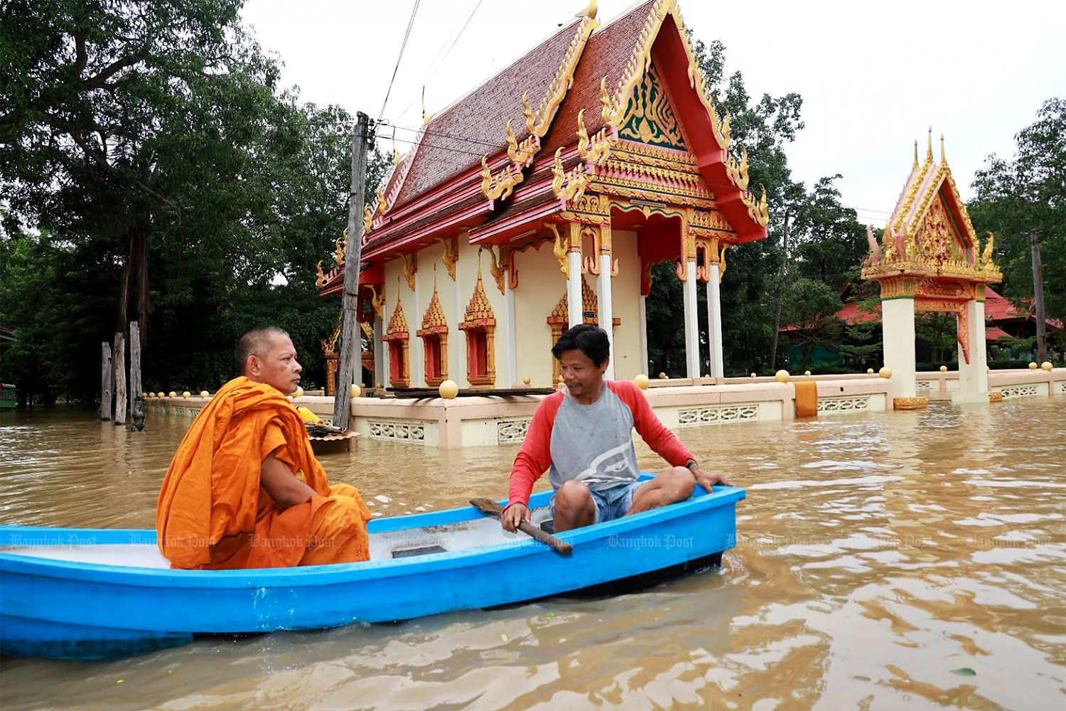 A monk and his helper sit in a boat as they pass through a heavily flooded community in Ban Kok Thai in Nakhon Ratchasima's Pak Thong Chai district on Tuesday. The district is one of worst-hit areas in a province battered by storms in the last couple of weeks. (Photo by Prasit Tangprasert)