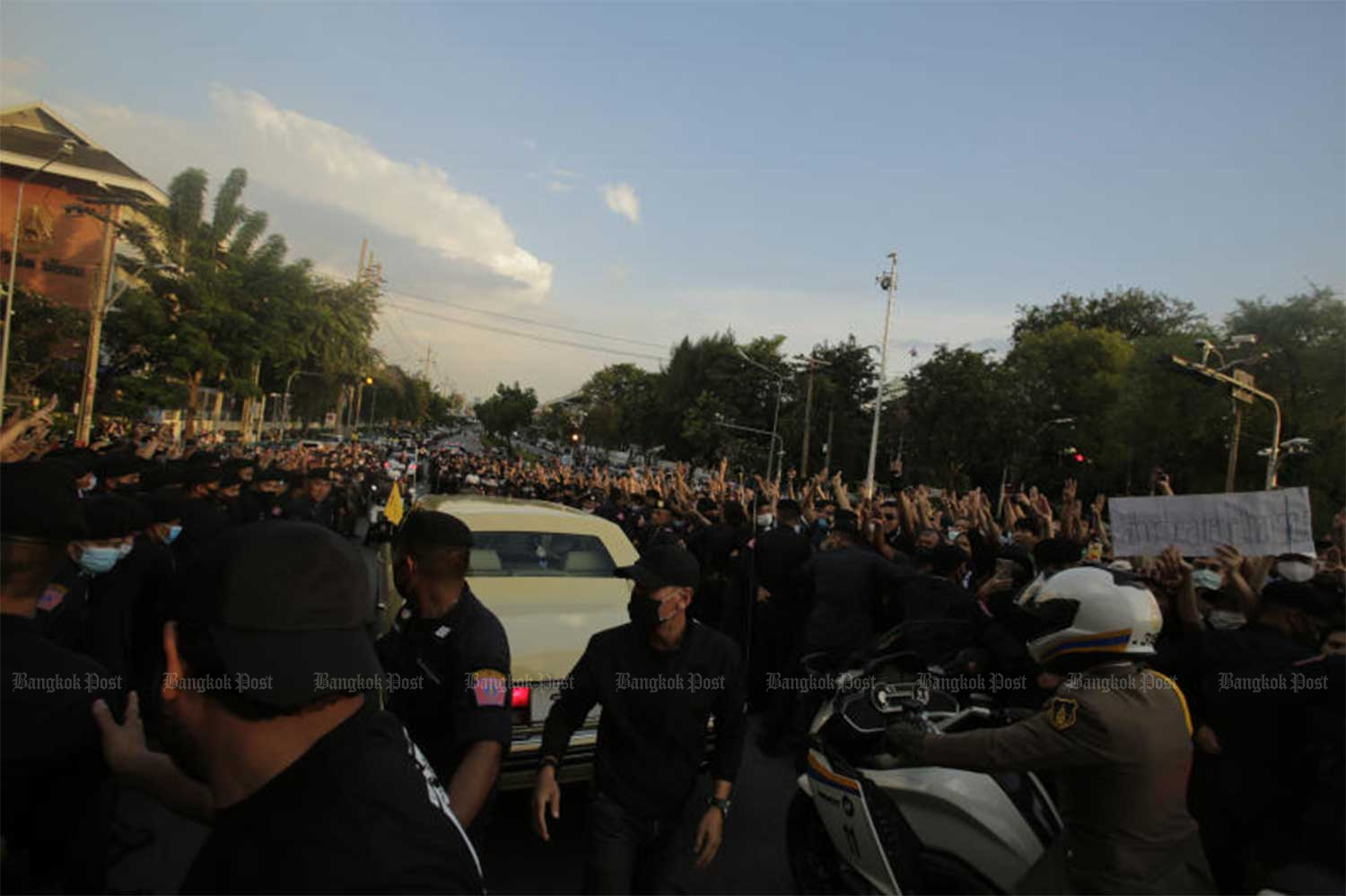 The royal motorcade carrying Her Majesty the Queen and His Royal Highness Prince Dipangkorn Rasmijoti passes through demonstrators near Government House on Oct 14. (Photo: Pornprom Satrabhaya)