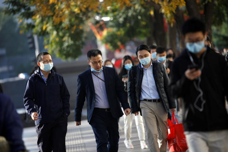 People wearing masks following the coronavirus disease outbreak are seen on a street during morning rush hour in Beijing on Monday. (Reuters photo)