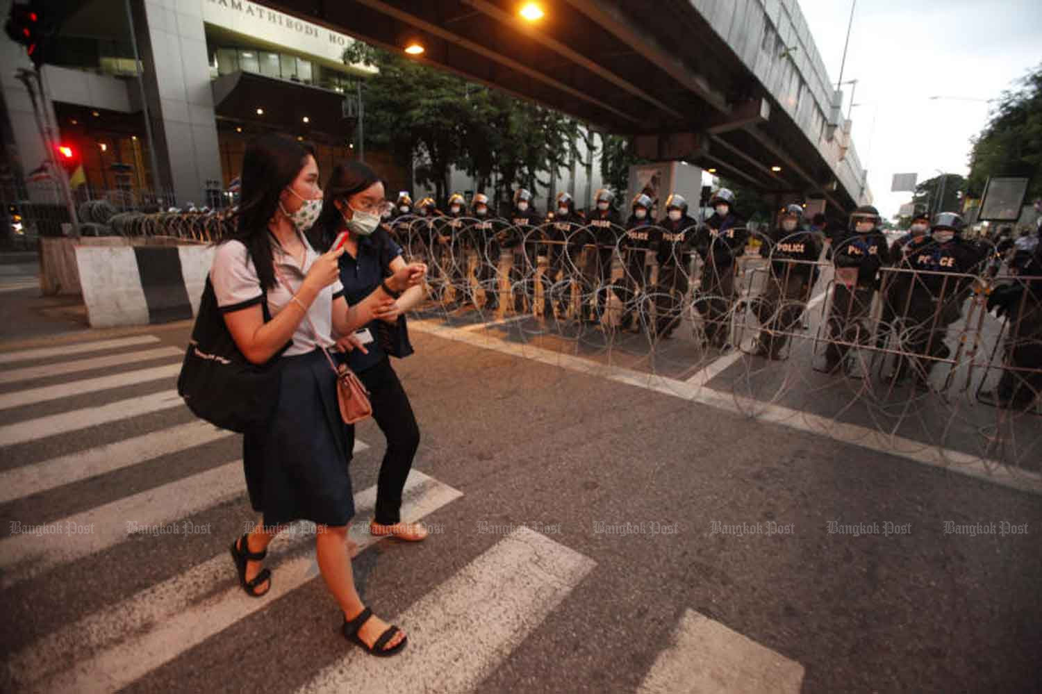 Two women in face masks walk past riot police blocking a road to Government House at Tuek Chai intersection, Bangkok, on Wednesday, when the country logged 10 new Covid-19 cases. (Photo: Pornprom Satrabhaya)