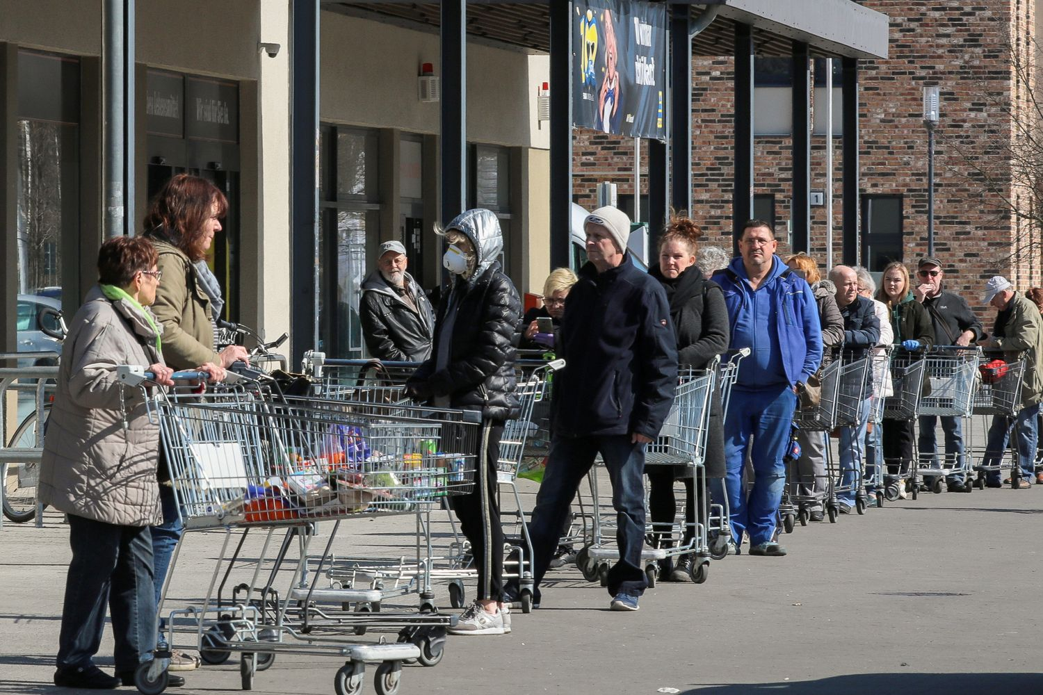 Shoppers leave as others wait in a queue to enter a supermarket in Schulzendorf near Berlin, during the coronavirus disease outbreak, in Germany, in March. (Reuters photo)