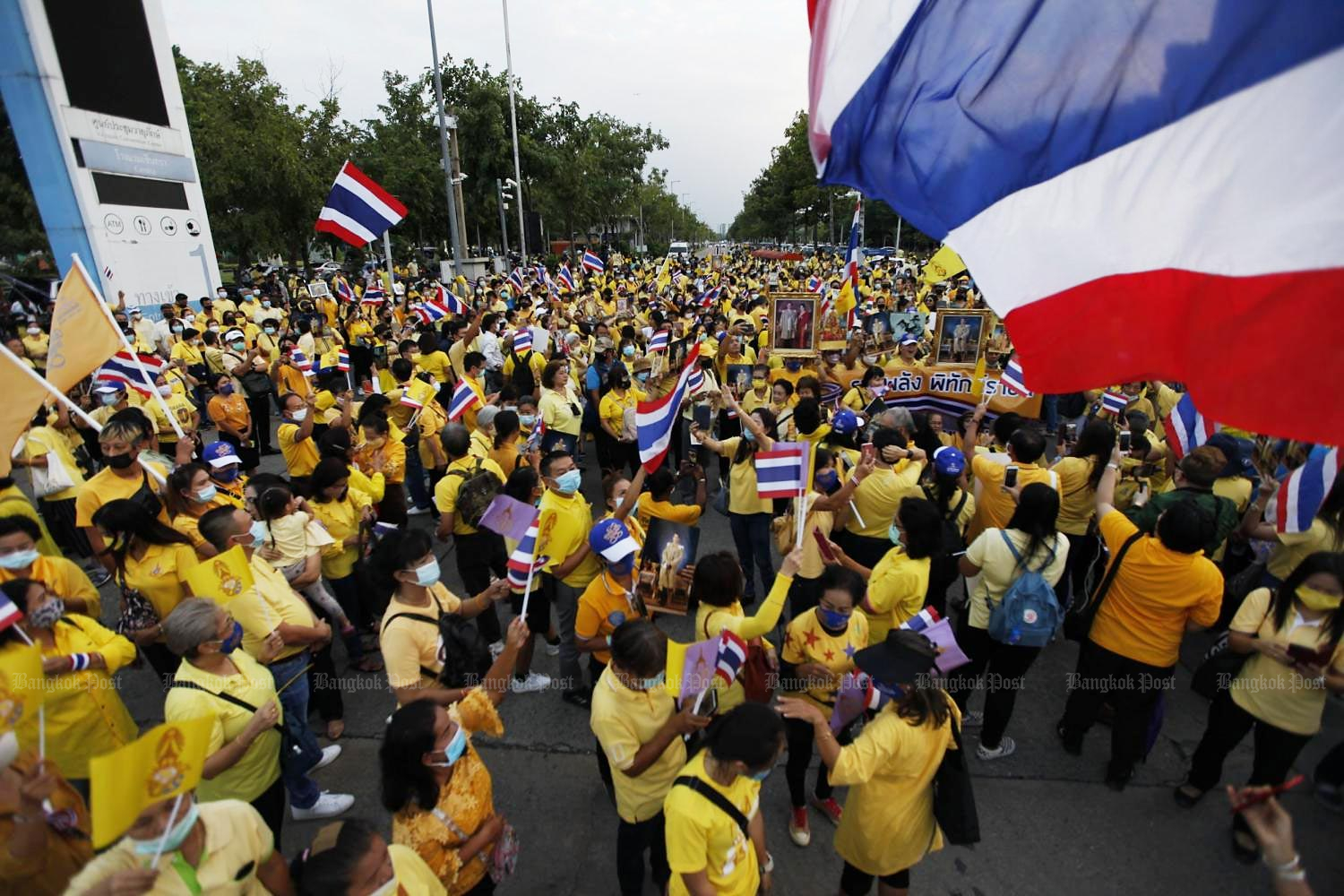 Yellow-clad people join a gathering outside the government complex on Chaeng Watthana Road yesterday. They dispersed after singing the national anthem and chanting 'Long Live the King'. (Photo by Pattarapong Chatpattarasil)