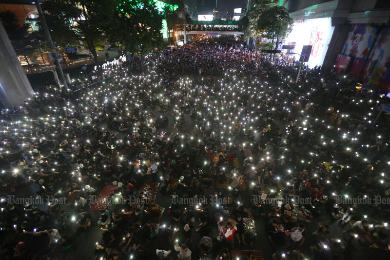 Protesters shine their mobile phone lights at Ratchaprasong intersection during a rally calling for the ouster of Prime Minister Prayut Chan-o-cha on Sunday. (Photo by Varuth Hirunyatheb)