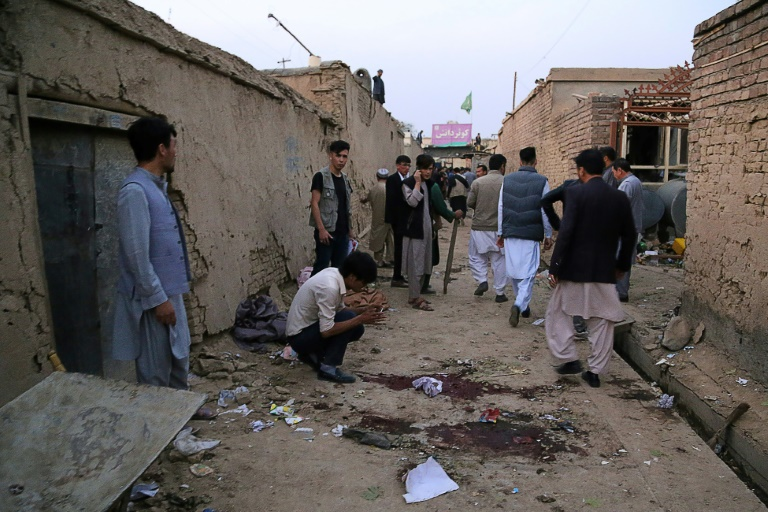 Residents gather near an education centre in the Afghan capital Kabul after a suicide bomber struck, killing at least 18 people.