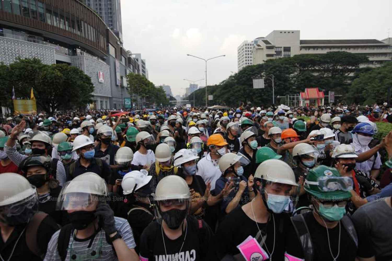 Demonstrators march on Sathon Road in Bangkok on Monday. (Photo by Wichan Charoenkiatpakul)
