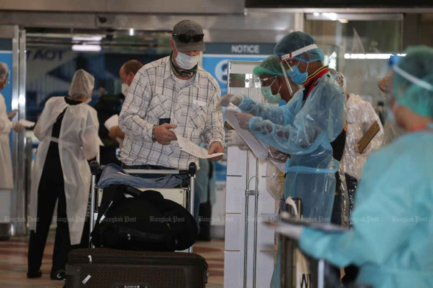 Disease control officials receive arrivals at Suvarnabhumi airport in Samut Prakan province on Monday. (Photo by Varuth Hirunyatheb)