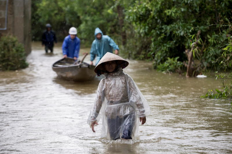 Residents wade along a flooded road at a village in Quang Tri province, Vietnam Oct 20, 2020. (Yen Duong/International Federation of the Red Cross (IFRC)/Handout via REUTERS)