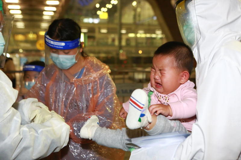 A baby boy cries as health officials test her mother for the coronavirus, as they and 37 other Chinese visitors arrived at Suvarnabhumi airport on Oct 20 under the special visa programme. (Photo: Somchai Poomlard)