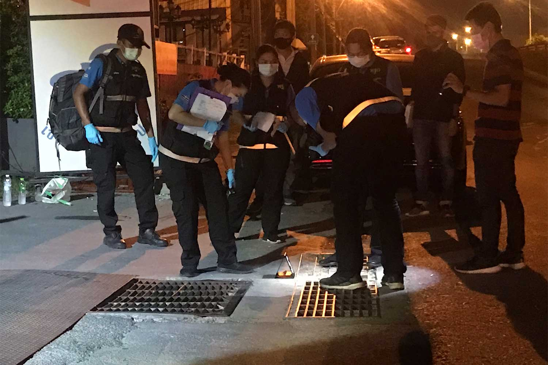 Polisi forensik mengumpulkan barang bukti di lokasi baku tembak di depan sebuah toko pijat di distrik Phasicharoen, Bangkok pada Selasa malam. Dua pria terluka. (Foto disediakan / Wassayos Ngamkham)