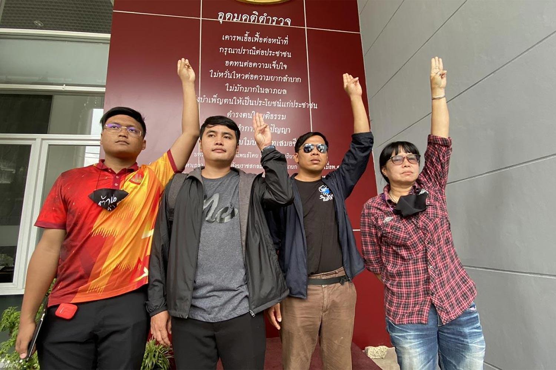 Protest leaders throw up the three-finger salute at Pathumwan police station. From left: Sirapob Phumpheungphut, Korakot Saengyenphan, Chartchai Kaedam and Suwanna Tarnlek.(Photo: police photo)