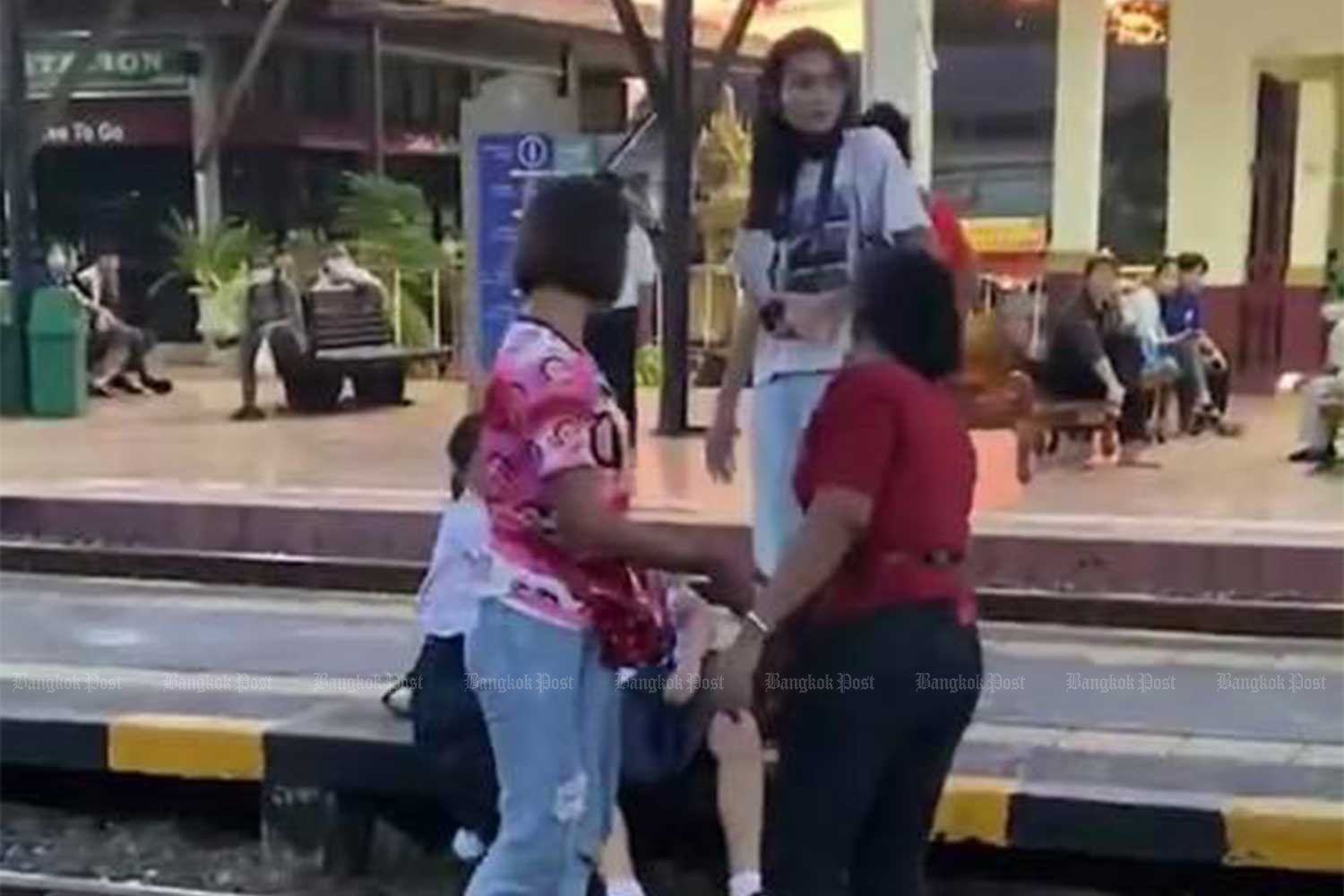the 45-year-old vendor, wearing red, slaps the face of the high school girl who did not stand up during the national anthem at Ayutthaya railway station on Tuesday. (Photo from เพื่ออยุธยา เพื่อประชาธิปไตย For Ayutthaya For Democracy Facebook page)