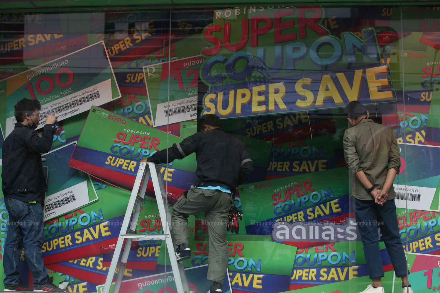 Workers decorate a banner highlighting the 'Super Coupon Super Save' promotion at the Robinson Department Store on Rama IV Road on Oct 2. (Photo by Apichart Jinakul)