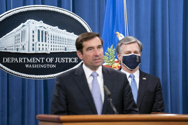 Assistant Attorney General John Demers (left) and FBI Director Christopher Wray announced the arrests of five Chinese agents for their roles in an operation targeting Chinese government opponents in the United States.