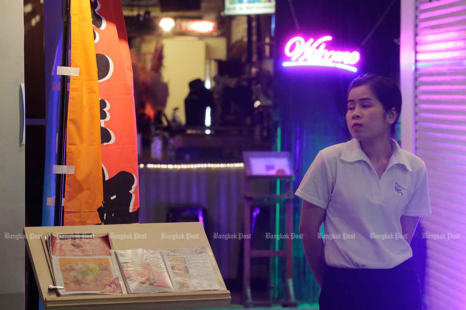 A restaurant employee waits to greet customers on Khao San Road, Bangkok, but business is still down in the formerly bustling tourist area because of Covid-19. (Photo: Pornprom Satrabhaya)