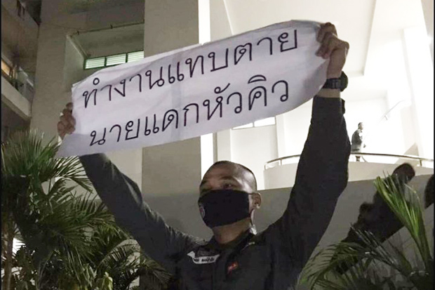 Pol Cpl Wutthichai Hongsamrong holds up a banner saying,
