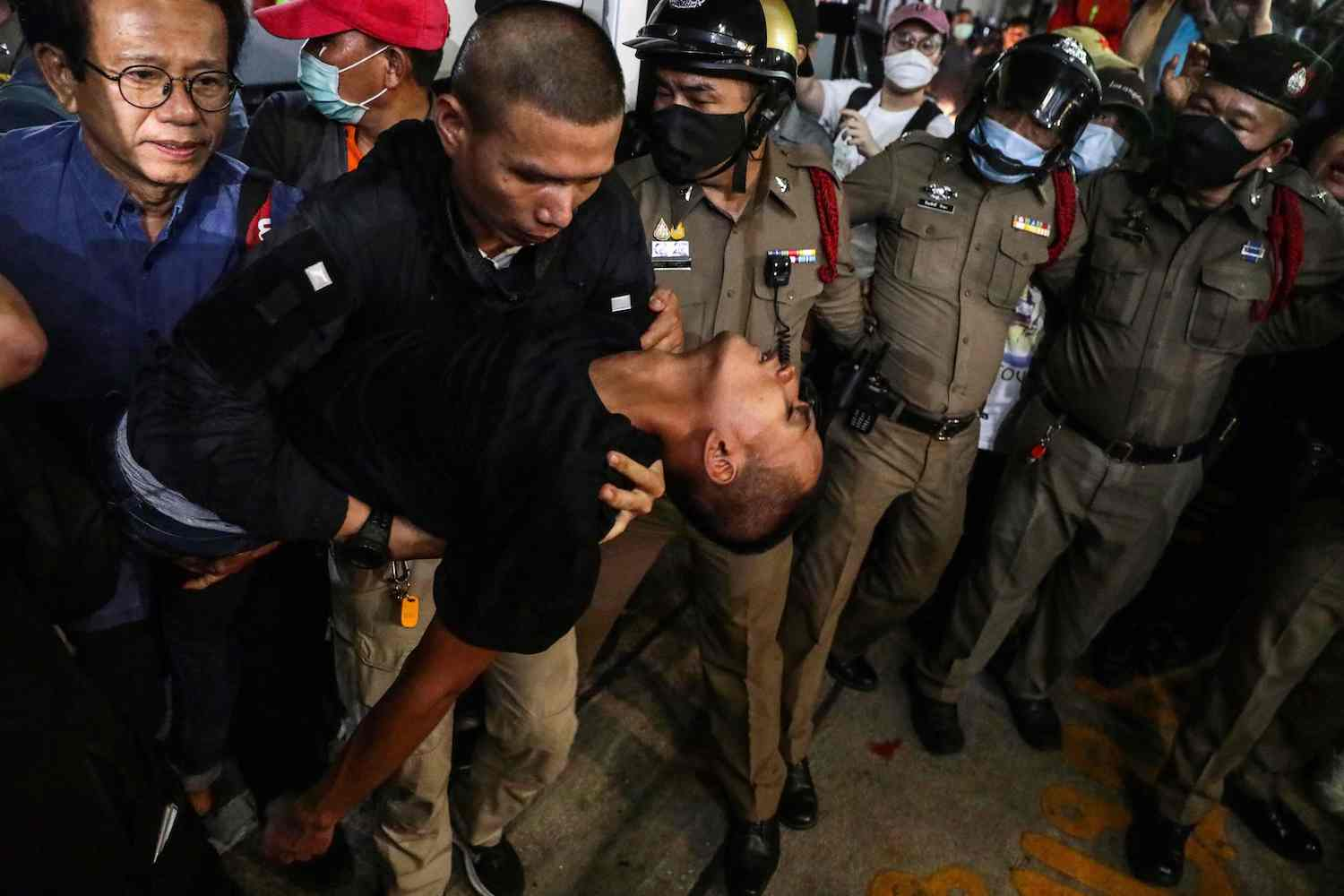 "An officer carries Panupong ""Mike"" Jadnok at the Pracha Chuen police station in Bangkok late Friday night. He reportedly fainted after a scuffle with police and was later taken to hospital. (AFP Photo)"
