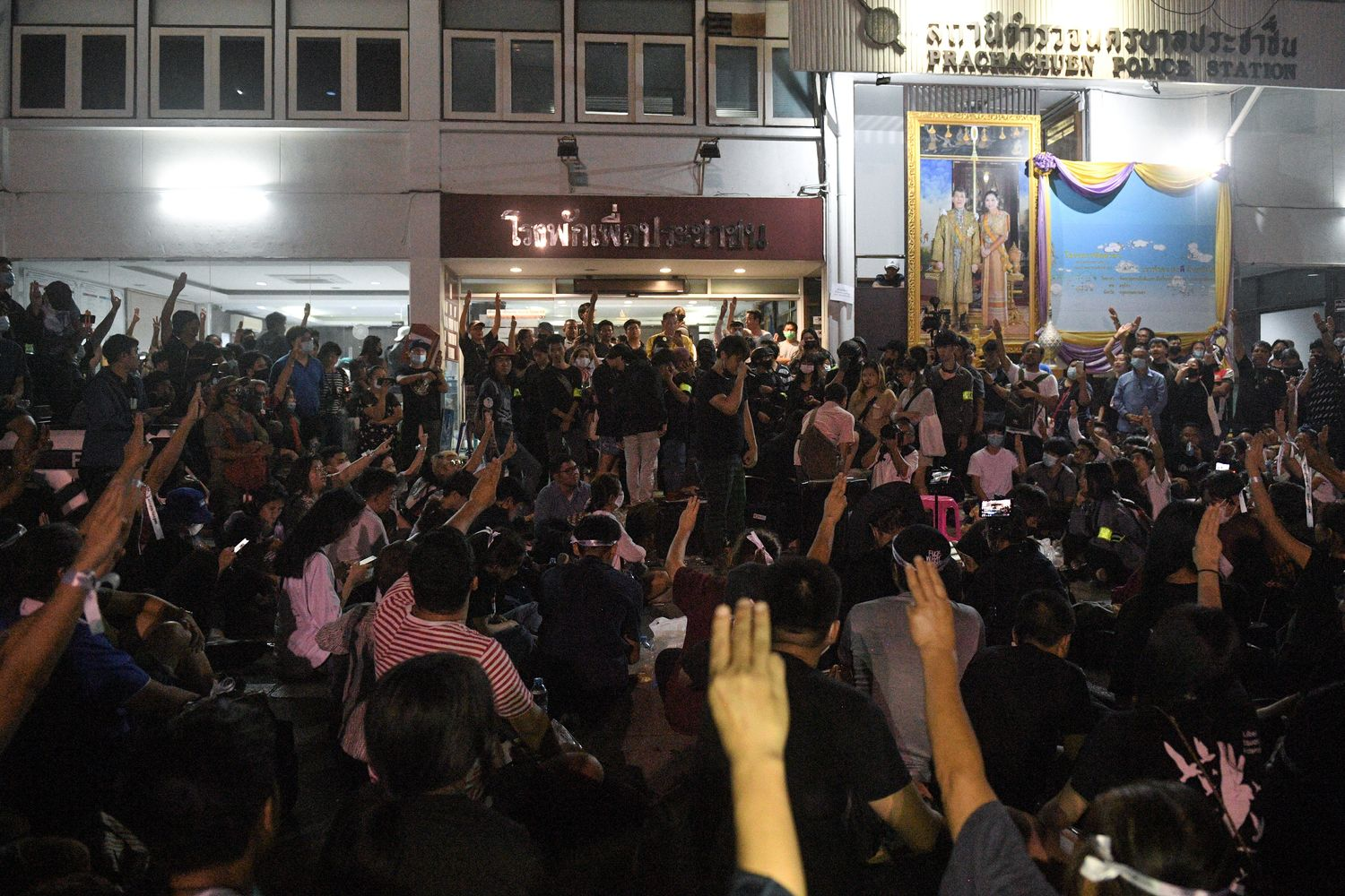 Demonstrators flash the three-finger salute as they gather outside the Pracha Chuen police station in Bangkok on Friday night. (Reuters photo)