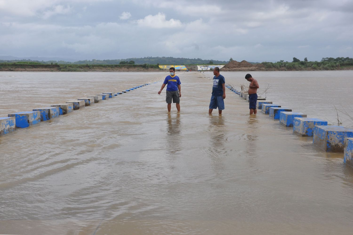 Residents wade across a flooded bridge over a swollen river in Ilagan town of Isabela province north of Manila on Saturday, ahead of the expected arrival of Typhoon Goni in the Philippines. (AFP Photo)